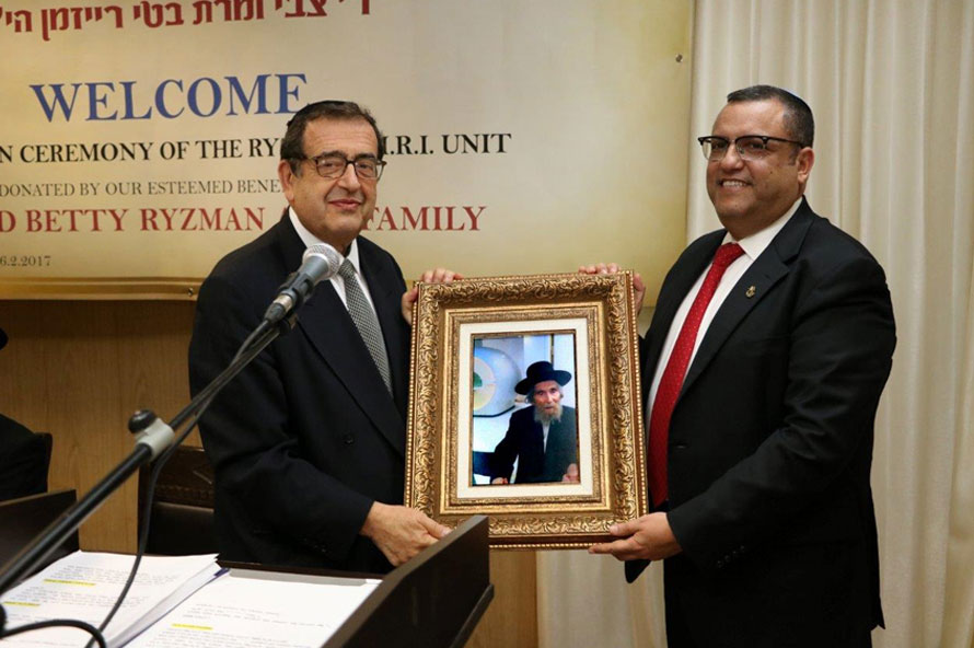 """יו""""ר הדירקטוריון רו""""ח משה ליאון מעניק לנגיד תצלום קביעת מזוזה במכון ע""""י מרן הגראי""""ל שטיינמן."""